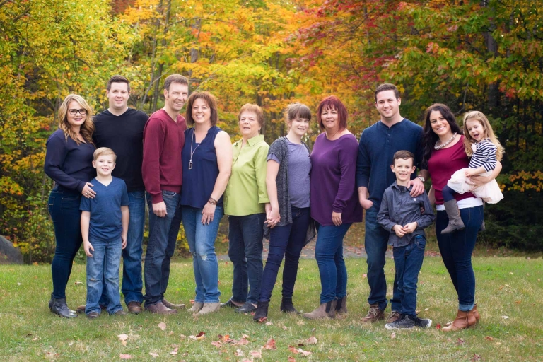 large family standing in field in autumn