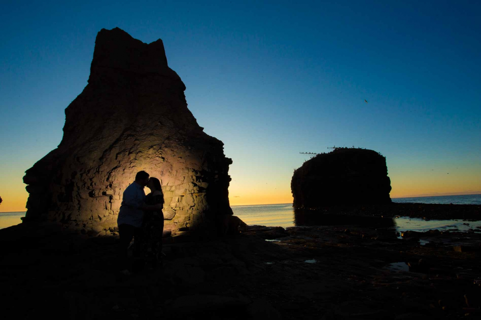 silhouette of couple kissing at Pokeshaw Rock New Brunswick