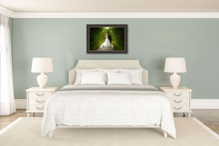 framed wedding photo hung above bed