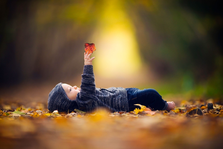 baby holding leaf on forest floor