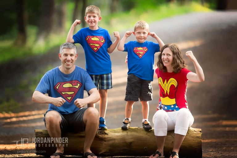 four people flexing on a log during a superman family photography session