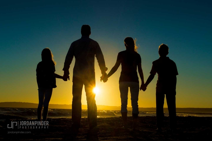 family of four standing together during a Crescent Beach sunset