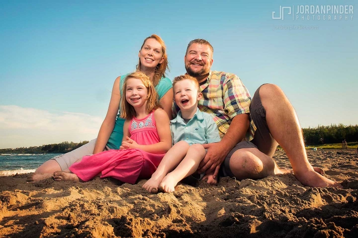 family of four sitting on beach smiling