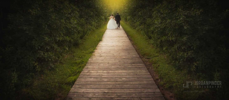 wedding photo of a married couple walking on boardwalk
