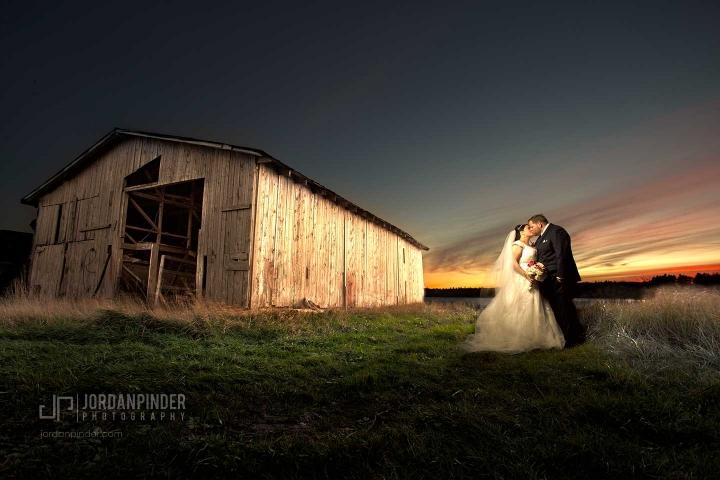 newlyweds posing near barn in Bridgewater Nova Scotia