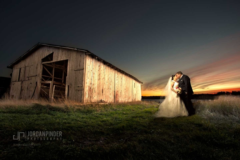 newlyweds posing near barn in Bridgewater Nova Scotia