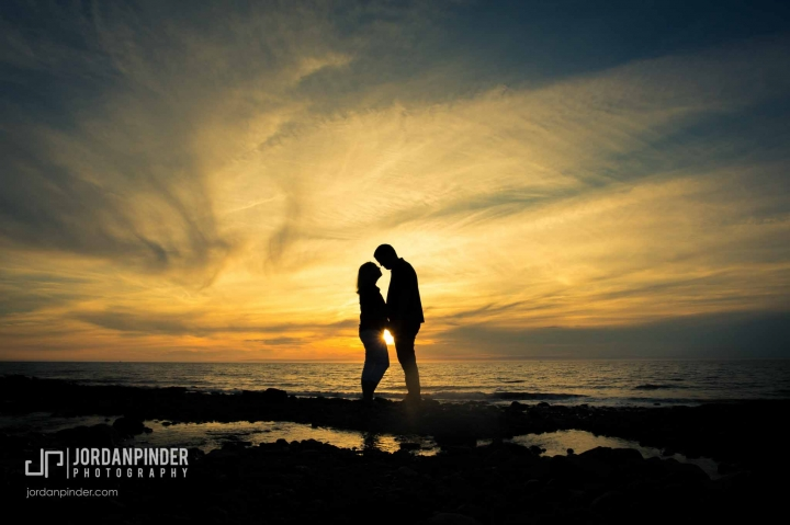 silhouette of engaged couple on the beach at sunset