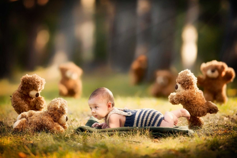 baby lying on ground with teddy bears outdoors