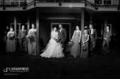wedding party standing casually in front of house