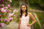 graduation photo of girl standing near magnolia
