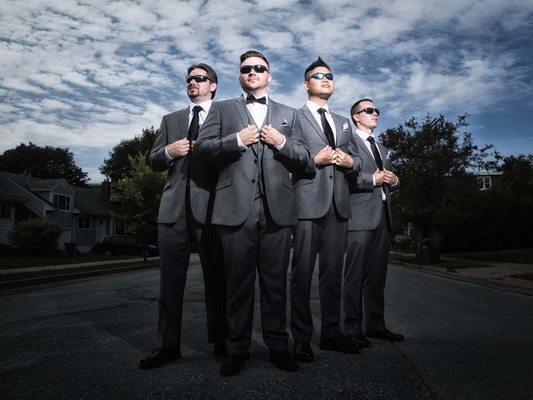 groomsmen standing tall in street