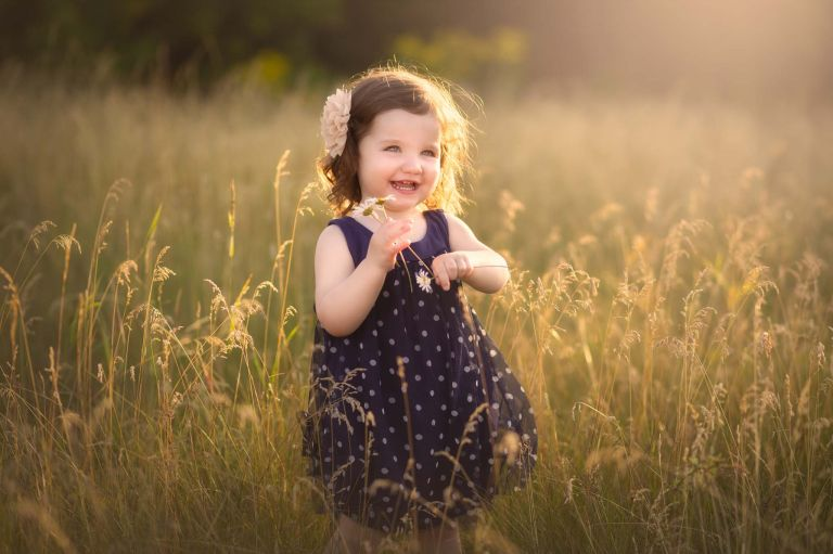 candid photography session with young toddler girl in field with daisies